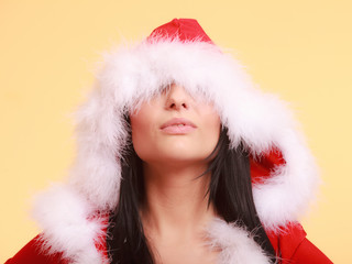 woman wearing santa claus costume covering her eyes on yellow