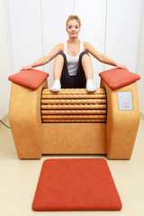 Girl in sportwear on relax massage equipment healthy spa salon