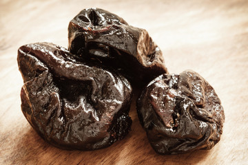dried plums prunes on wooden table