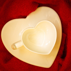 Empty heart shaped cup on red