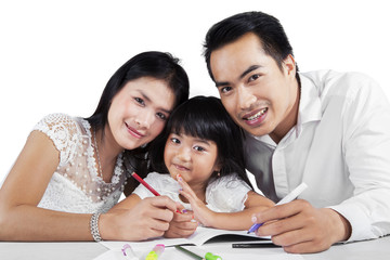 Cheerful family doing schoolwork together