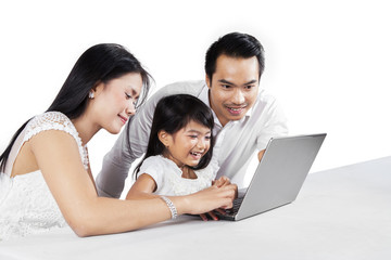 Cheerful family with laptop in studio