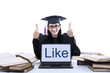 Female graduate thumbs up with like on laptop