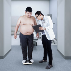 Doctor record the body mass of patient