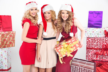 Three alluring women wearing Christmas hats
