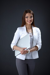 Young woman holding a laptop, isolated on grey background