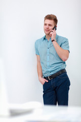 Portrait of a handsome young man with phone on white  background