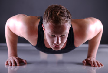 Fitness man doing push ups on floor, isolated grey background