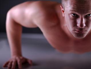 Fitness man doing push ups on floor, isolated grey background