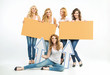 Five attractive women holding boards and arrows