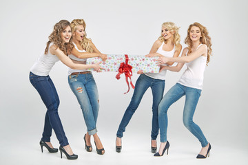Four cheerful girls fighting for gift