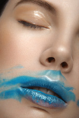 Girl with perfect skin and blue makeup on her ears