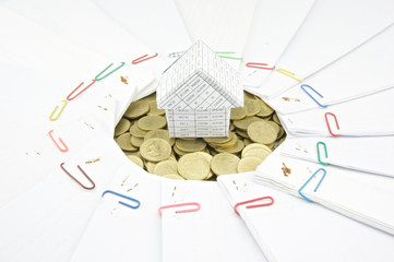 House on pile of gold coins with document