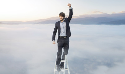 Handsome man on the ladder above the clouds