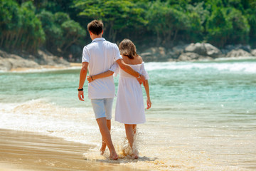 hugging couple walking on beach together