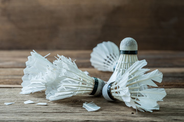 Shuttlecock with parts of its feathers scattered on wooden