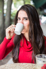 Portrait of happy beautiful brunette with mug in hand and drinki