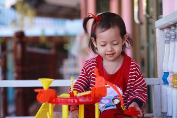 Smile kid girl playing toys.