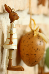 Osterhasenmädchenfigur mit Ei an Mauer