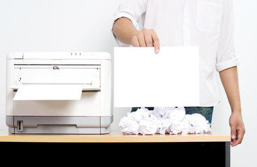 Businessman showing blank paper near color printer on table