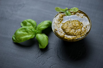 Glass bowl with basil pesto on a black wooden surface, close-up