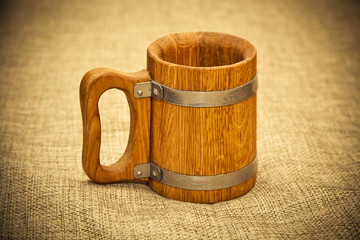 Old wooden mug stands on the material of burlap