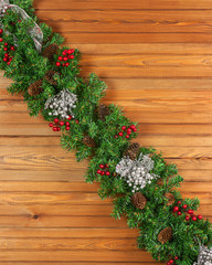 Garland with Christmas ornaments and pine cones on wooden backgr
