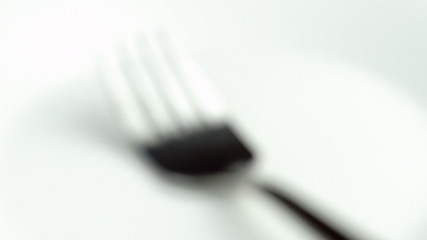 Zooming towards blurred macro of silver kitchen fork