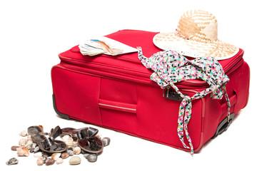 Красный чемодан с шляпой на белом фоне