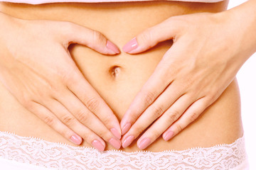Hands on a female belly, isolated on white