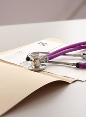 A medical stethoscope on a folder, on the table