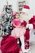 little girl sits on a lap at Saint Nicolas about a New Year tree