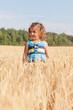 little girl in a summer sundress goes across the field of wheat