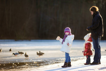 Father and his daughters feeding ducks at winter
