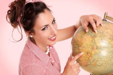 schöne Frau zeigt auf Globus