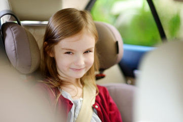 Adorable girl sitting safely in car seat