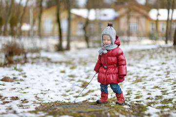 Adorable little girl having fun on winter day