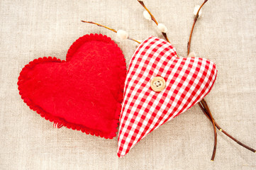 Two homemade sewed red cotton love hearts with spring willow twi