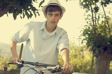 young boy with bicycle in summer