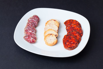 Spanish chorizo tapa over black table.
