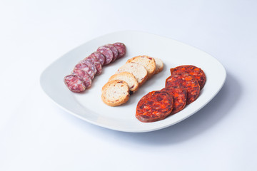 Spanish tapa of sliced chorizo in white dish.