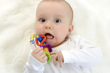 Baby boy having fun at home with teether
