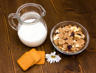 Jug of milk and cereal in bowl on wooden table seen from above