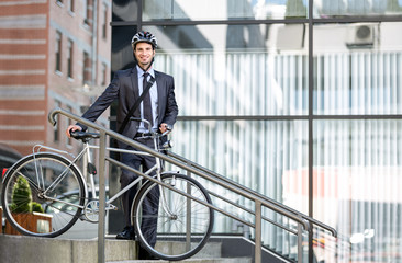 Handsome young businessman carrying bicycle down steps
