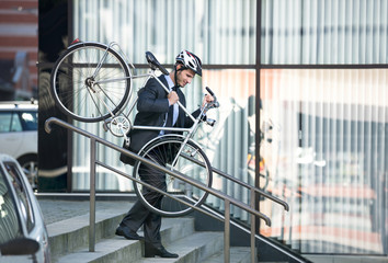 businessman carrying his bike