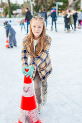 Cute little girl learning to skate with the support