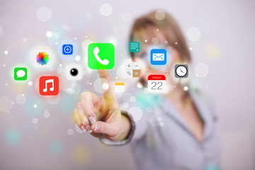Young businesswoman pressing colorful mobile app icons with boke