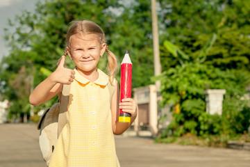 happy schoolgirl standing on the road