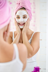 Young  woman applying facial cleansing mask