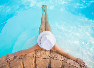Woman in big hat relaxing on the swimming pool on sunny day.